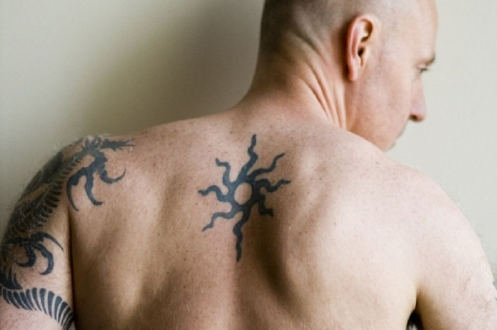 Small Tribal Sun Tattoo On Upper Back Men Pictures